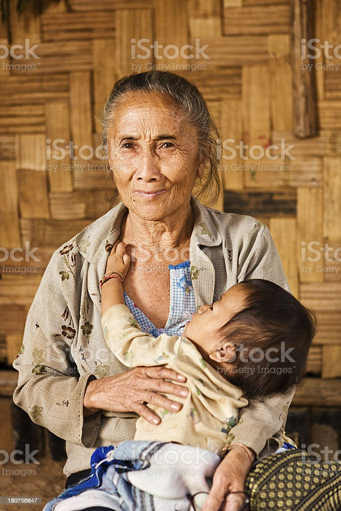 Old woman from the hill tribe holding her granddaughter royalty-free stock photo