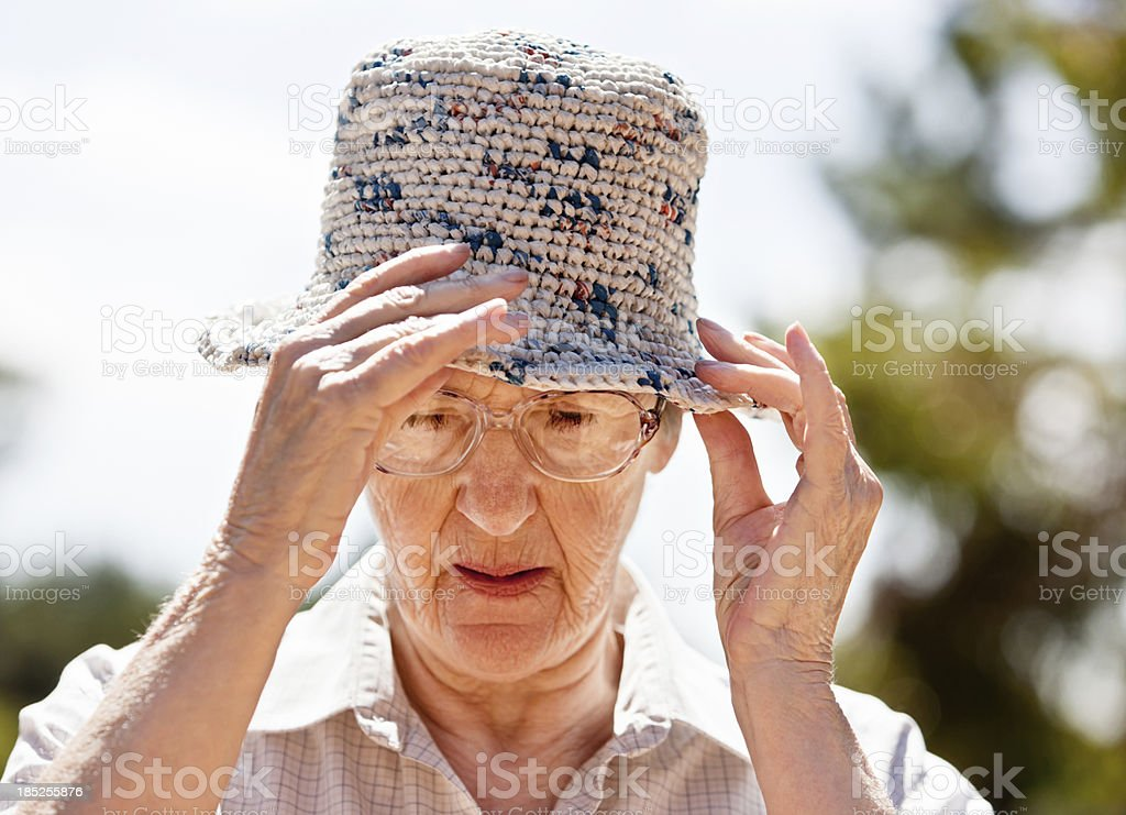 Old woman frowns as she adjusts sunhat stock photo