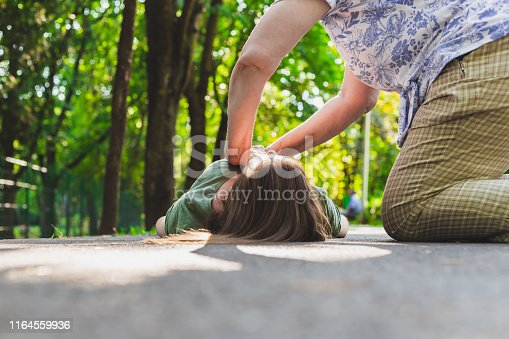 Unconscious fainted girl having cpr done by an old woman – Teenager lying on the ground while receiving cardiopulmonary resuscitation by an elder citizen