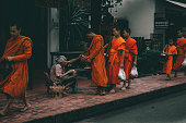 istock old Woman giving food to the monks in luang Prabang 1248569326
