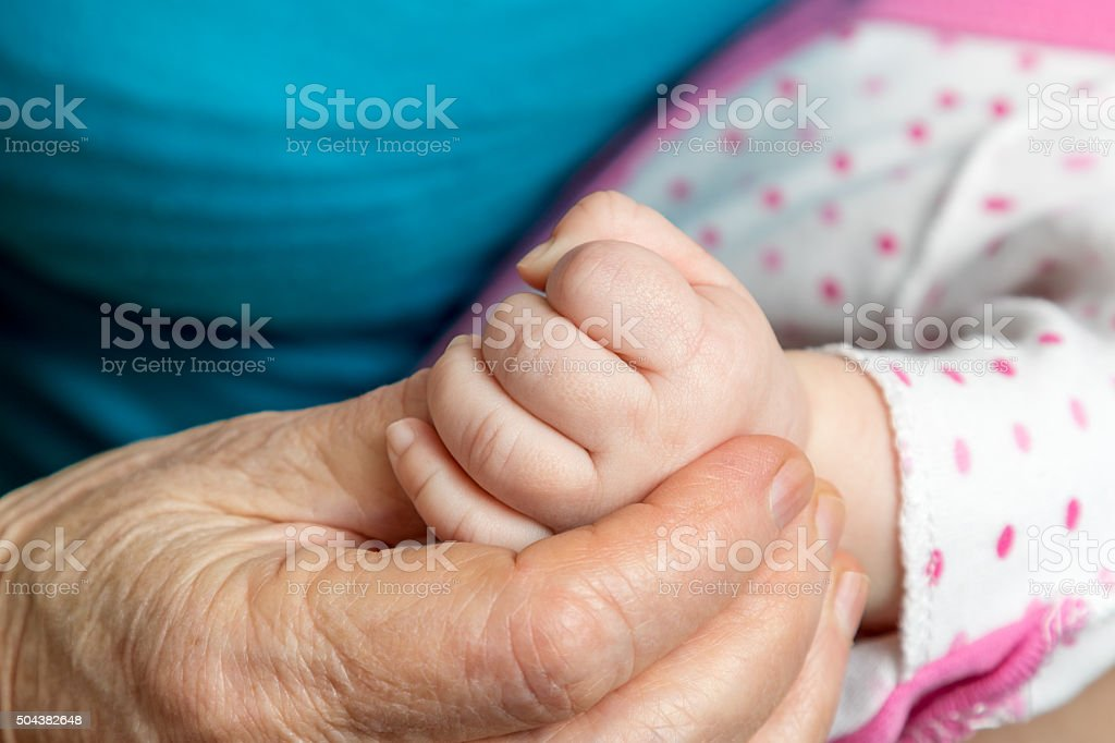 Old woman hand holding palm baby Hand old woman holds in her hand an infant hand closeup Adult Stock Photo