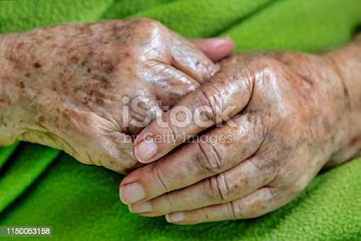 Old woman hands on blanket