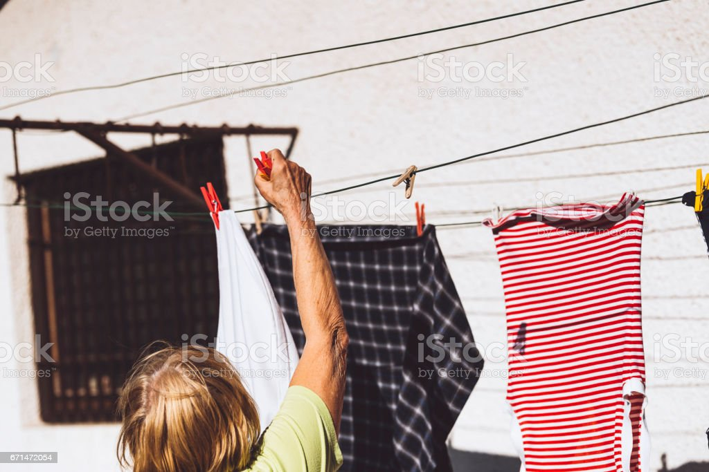 Old woman hanging freshly cleaned clothes in her back yard on a...