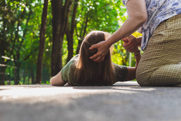 Old woman helping a fainted girl to get back on her feet Fainted girl helped by an old woman – Teenager trying to get back on her feet while receiving support from an elder woman taking pulse stock pictures, royalty-free photos & images