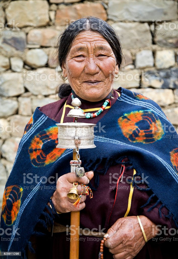 Old woman holding hand prayer wheel stock photo