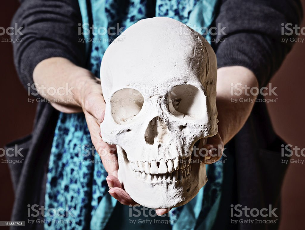 Old woman holding human skull: life is short, death inevitable stock photo