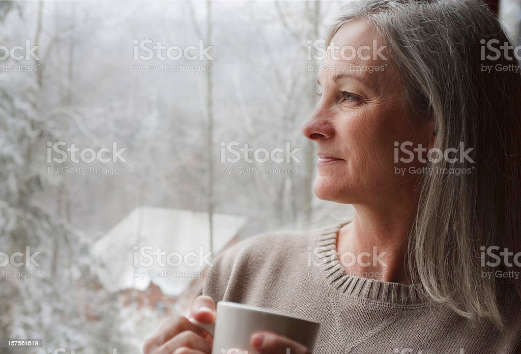 Old woman holds a mug while looking at snow from the window royalty-free stock photo