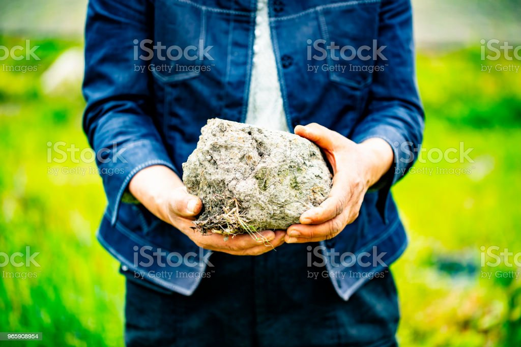 Old woman holds in her hands a big soil. - Royalty-free Adubo - Fenómeno Natural Foto de stock
