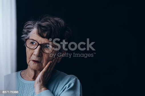 istock Old woman in dark room 837175066