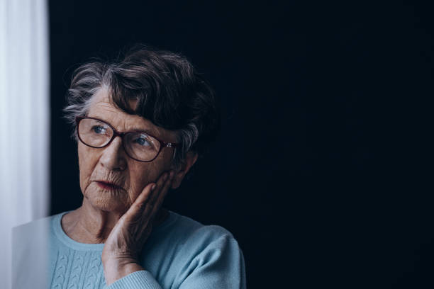 Old woman in dark room stock photo
