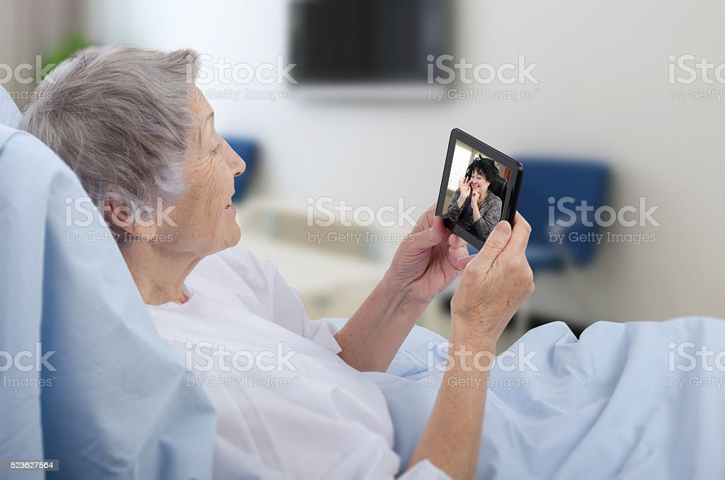 Old woman in hospital ward has video chat stock photo
