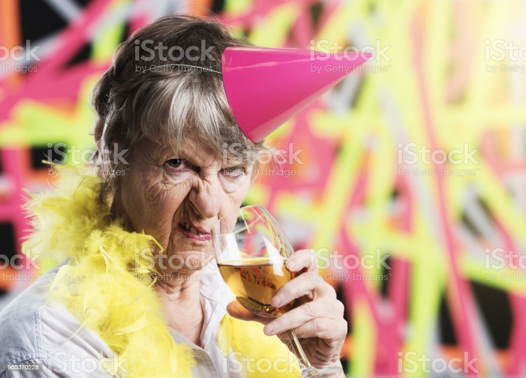 Old woman in party gear with champagne is very irritated zbiór zdjęć royalty-free
