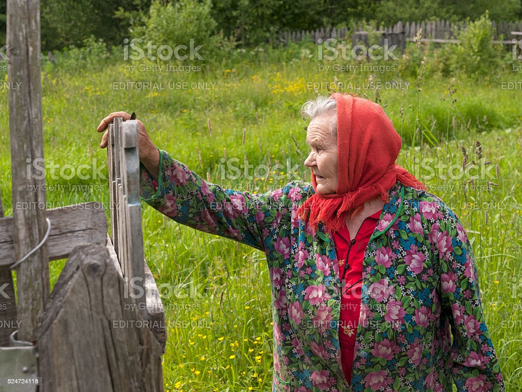 Old woman in red headscarf stands against blurred garden background stock photo