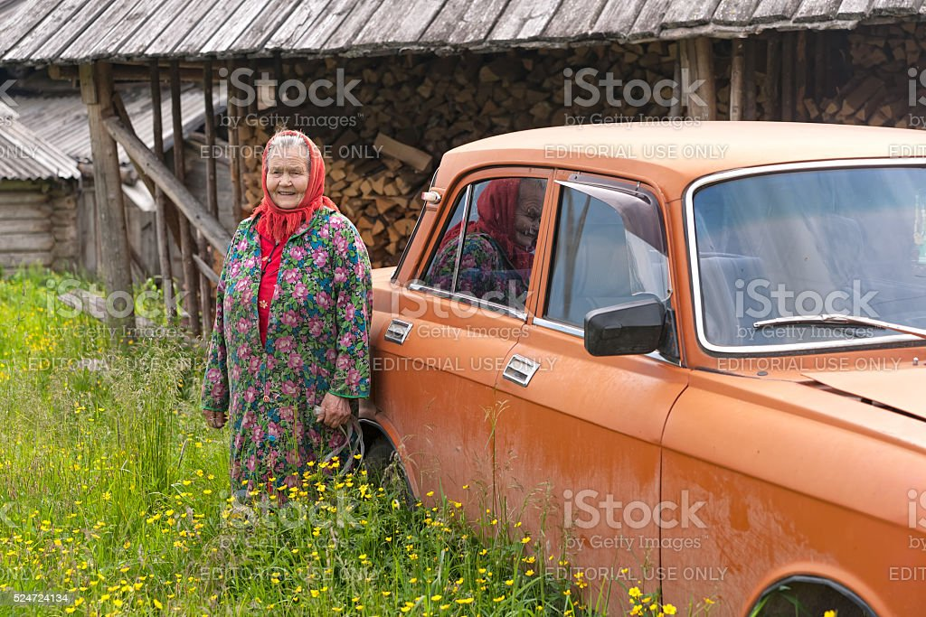 Old woman in red headscarf stands near orange car stock photo