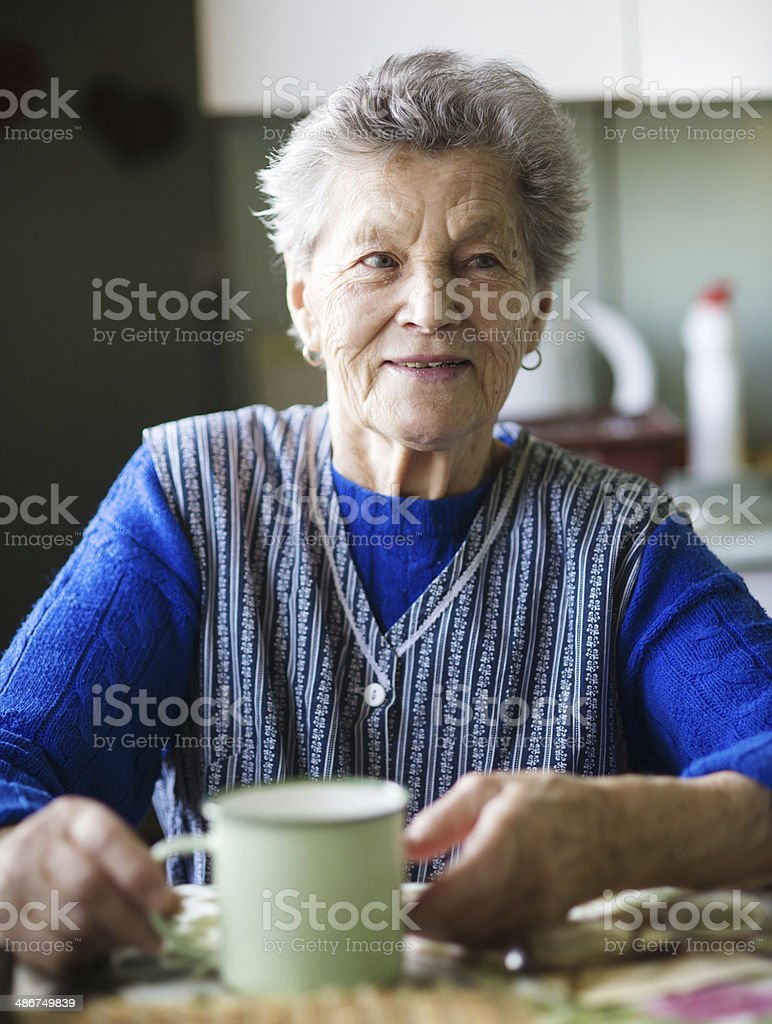 Old woman in the kitchen stock photo