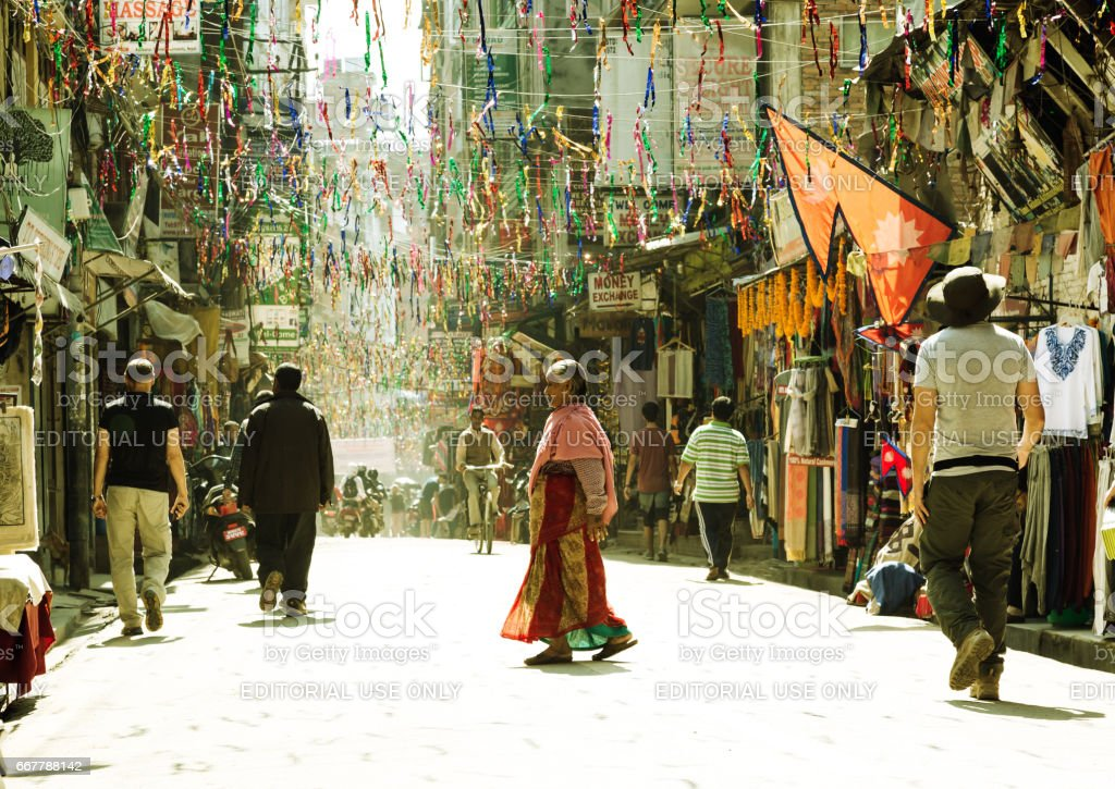 Old Woman in traditional Clothing walking on Street in Kathmandu stock photo