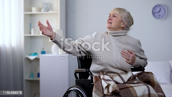istock Old woman in wheelchair feeling chest pain, asking help, heart attack, hospital 1150489378