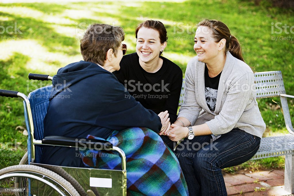 Old woman in wheelchair holds hands with smiling young women royalty-free stock photo