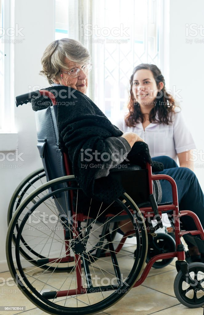 Old woman in wheelchair looks round from her friendly caregiver royalty-free stock photo