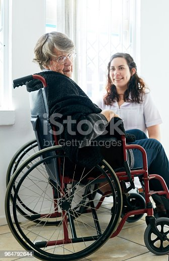 Old Woman In Wheelchair Looks Round From Her Friendly Caregiver Stock Photo & More Pictures of 1920-1929