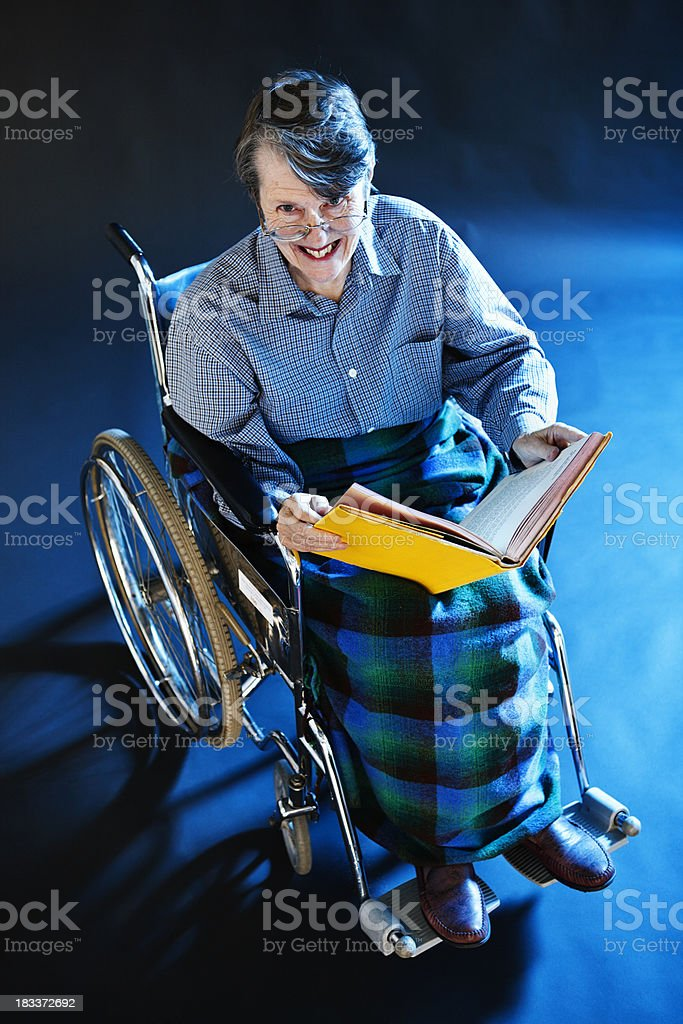Old woman in wheelchair smiles up from book royalty-free stock photo