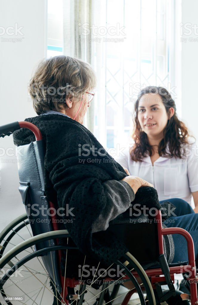 Old woman in wheelchair talks to her friendly caregiver royalty-free stock photo