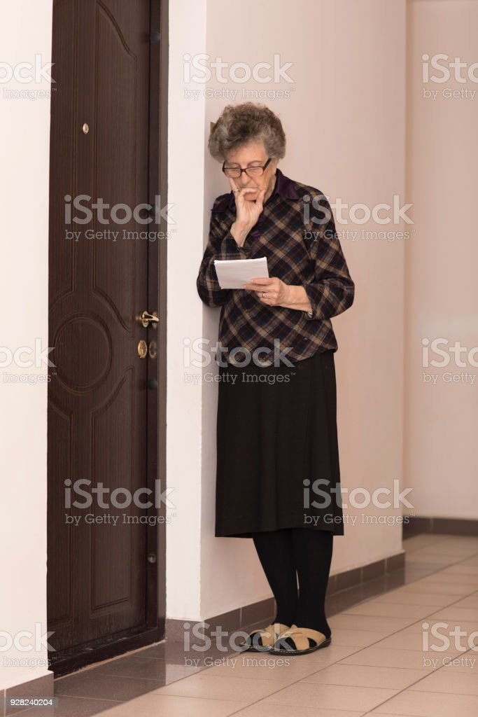 Old woman is knocking at the neighbour door stock photo