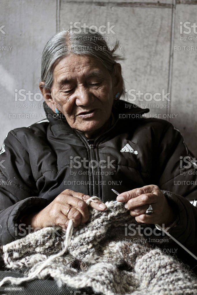 Old woman knitting a scarf stock photo