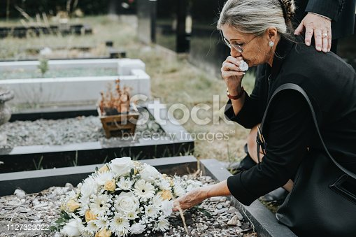 Old woman laying flowers on a grave