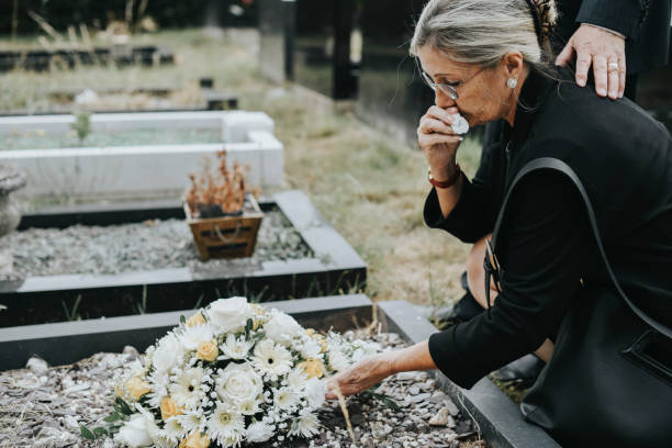 Old woman laying flowers on a grave stock photo