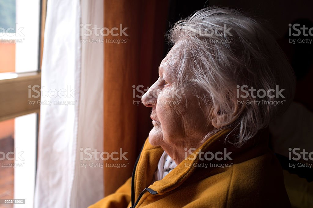 old woman looking in a window royalty-free stock photo