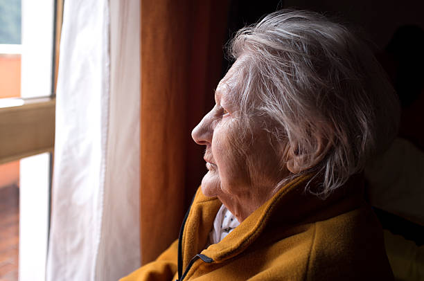 old woman looking in a window stock photo