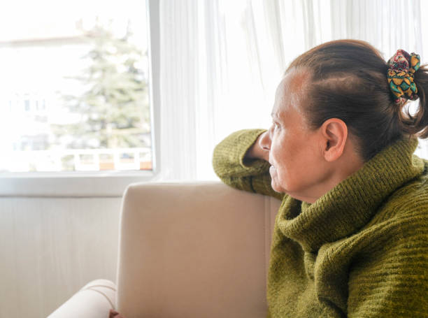 old woman looking out the window. stock photo