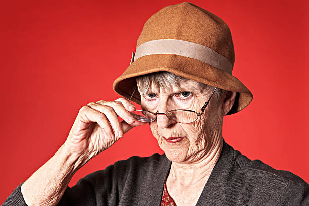 vieille femme looks disapprovingly dessus des lunettes à la caméra - indiscret photos et images de collection