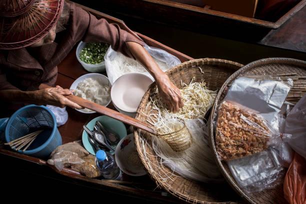 oude vrouw thaise noedels eten maken door zeilen in de lokale drijvende markt in de boot - thai food stockfoto's en -beelden