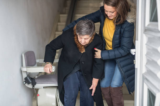 Old woman moving down the stairs stock photo
