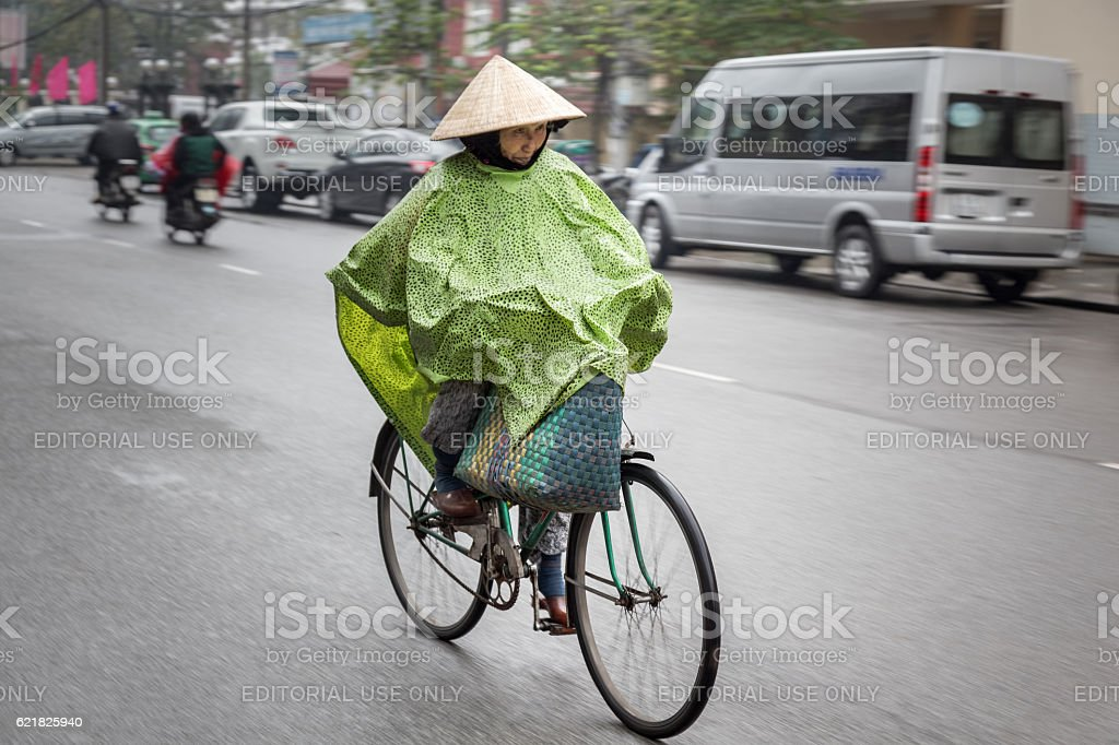 Old woman on a bike dressed for rain stock photo