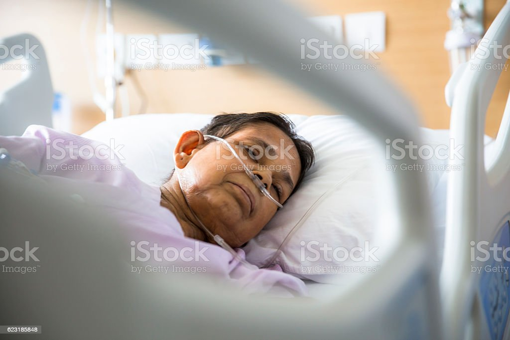 Old woman on Hospital bed, Oxygen tubes in her nose stock photo