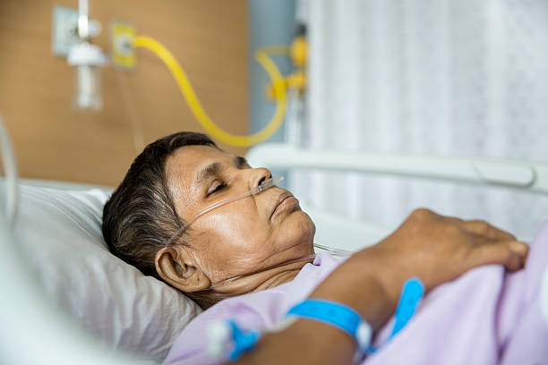 Old woman on Hospital bed, Oxygen tubes in her nose Old woman patient lying on Hospital bed with Oxygen tubes in her nose. She has her eyes closed. oxygen tube stock pictures, royalty-free photos & images