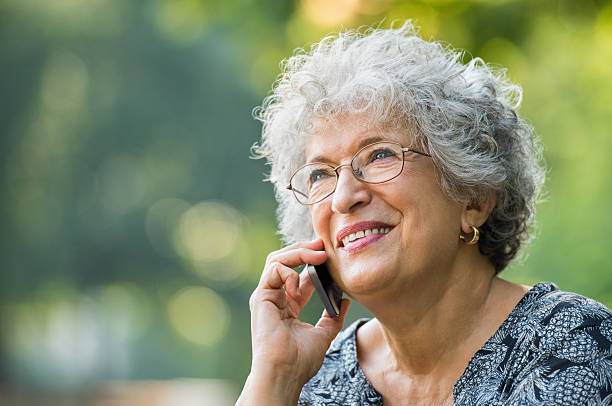 old woman on phone - older woman phone stock photos and pictures