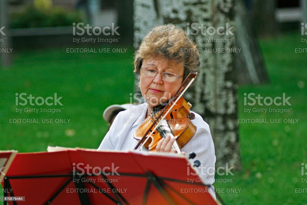 Old woman playing violin in the street in the City Day in Volgograd stock photo