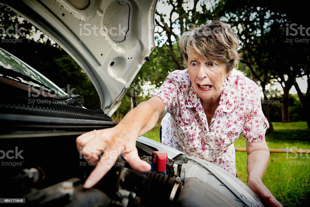 Old woman pokes engine of broken-down car, in a panic stock photo