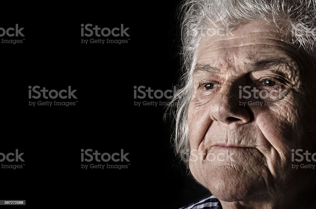 Old woman portrait, close-up face on dark background. Lizenzfreies stock-foto