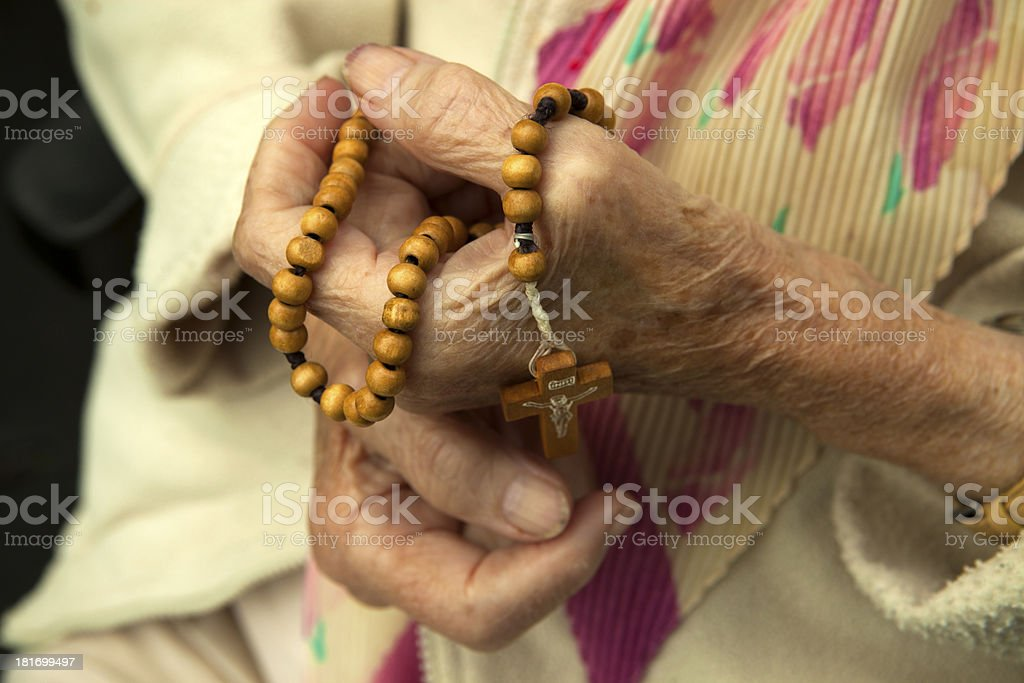 Old woman prays the rosary royalty-free stock photo
