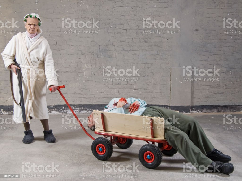 Old woman pushing dead man in trolley stock photo