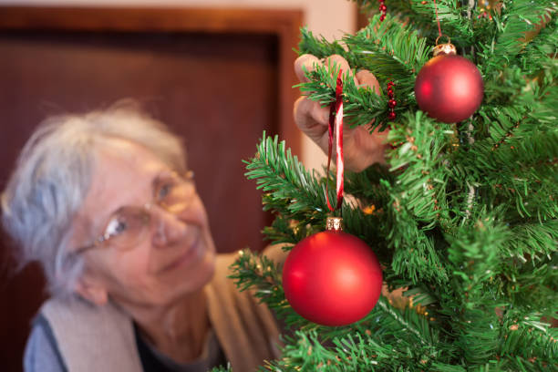 old woman putting ornaments on christmas tree - alte weihnachtsbäume stock-fotos und bilder