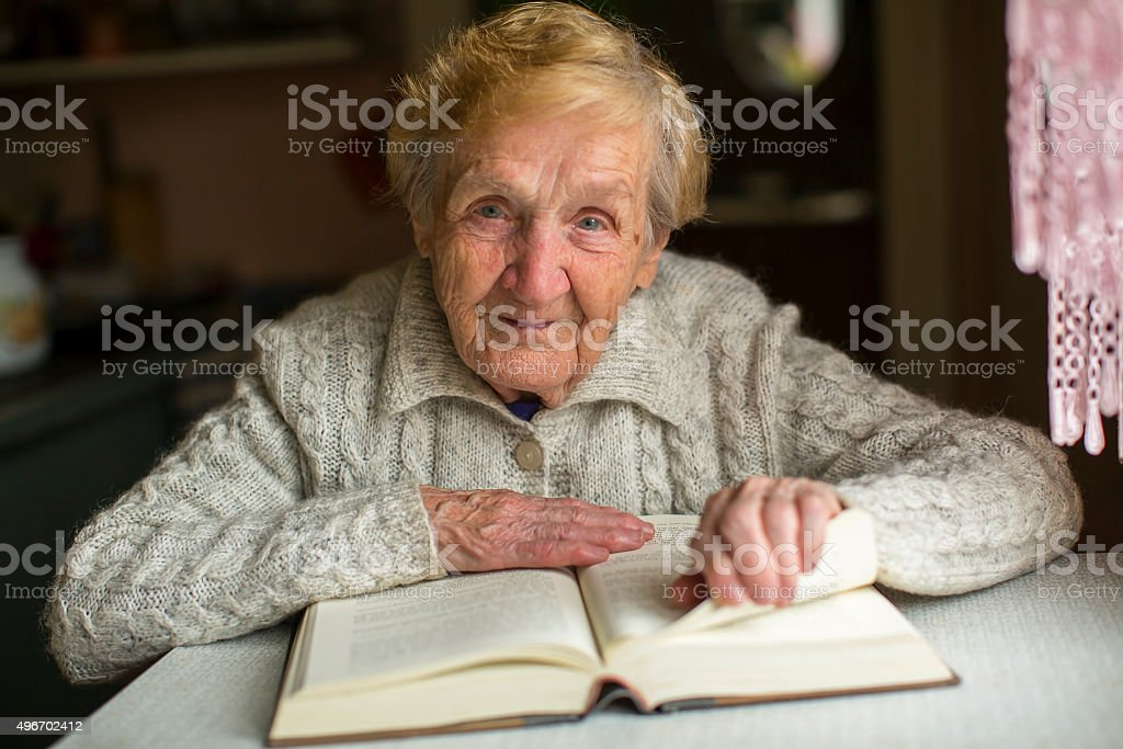 Old woman reading a book sitting at the table. stock photo