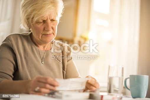 Senior woman sitting at home and reading medical instructions for a medicine.