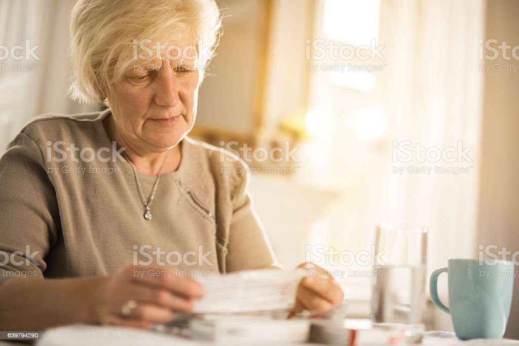 Old woman reading instructions for a medicine. stock photo