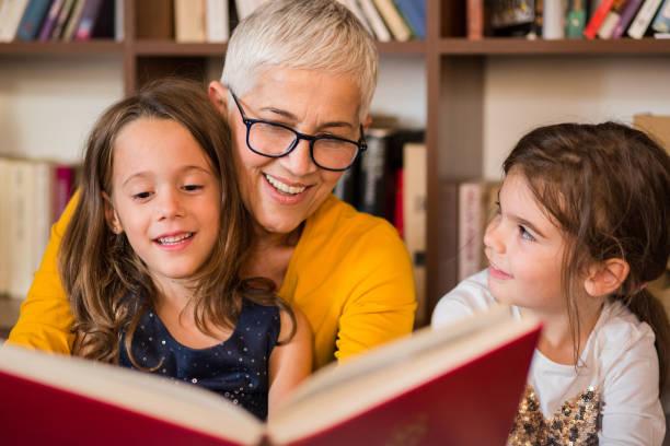 alte frau liest, enkelinnen - geschichten für kinder stock-fotos und bilder